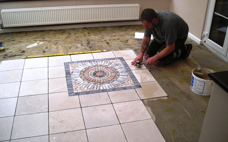 Mosaic Centre piece seen being laid with an Italian 400x400 lime stone tumble tiles.