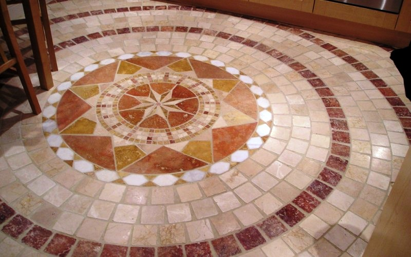 Mosaic centre piece laid in the middle of the area of the kitchen. With Italian 100x100 tumble marble laid around the mosaic to give a ripple effect.